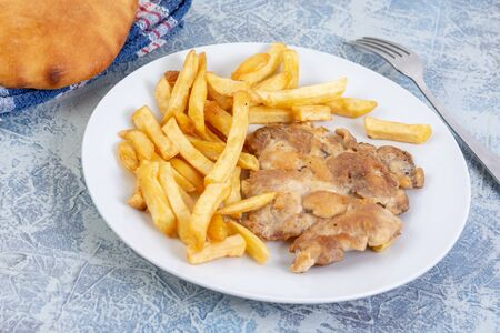 Grilled chicken drumstick with potatoes on blue background.