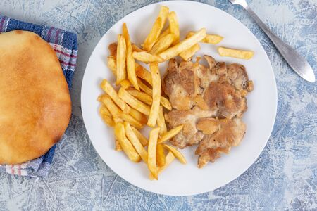 Top view of grilled chicken drumstick with french fries and bread. Stock Photo