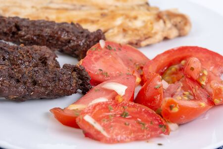 Grilled kebabs and chicken meat served with fresh tomato salad.
