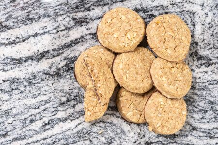 Pile of round chocolate biscuits on the grey marble background.