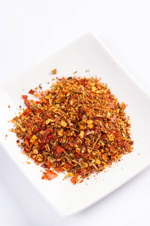 Grated red hot chilli paprika served on the plate.