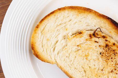 Toasted bread served on the white plate. Zdjęcie Seryjne