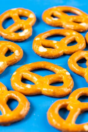 Pile of pretzels on the blue wooden background.