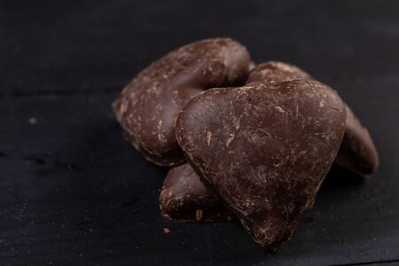 Chocolate candy heart shaped on the black background.