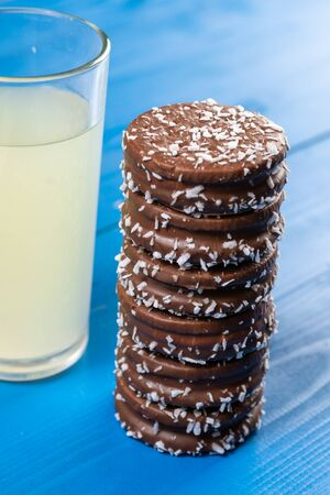 Chocolate cookies with coconut and the lemonade on the blue table.