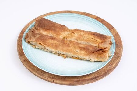 Meat pie served on the blue plate. Traditional burek with meat served on the plate.