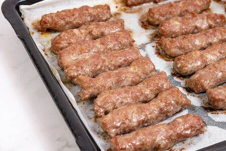 Fried minced meat kebabs on the baking tray. Traditional balkan meat food.