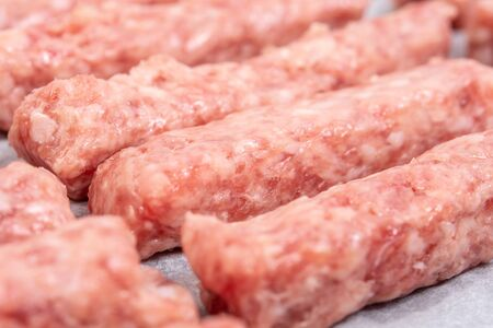Fresh and raw minced meat kebabs on the baking tray ready for baking.