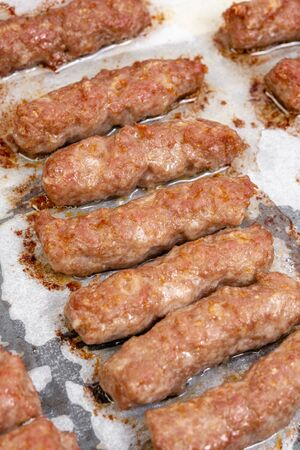 Fried minced meat kebabs on the baking tray. Traditional balkan meat food