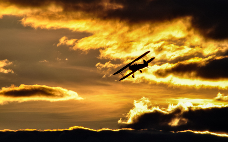 Flying biplane on a background of clouds and sunset Stock Photo