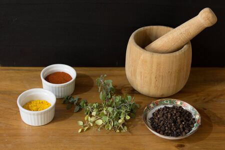 Spices and mortar on wooden table