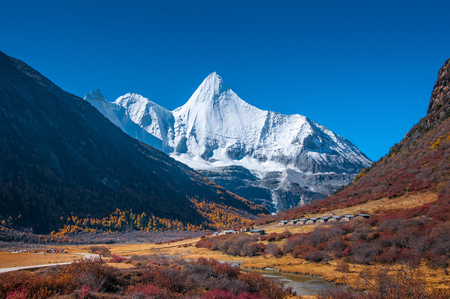 Autumn scenery in Yading Nature Reserve, Daocheng county, Ganzi Tibetan Autonomous Prefecture, Sichuan province of China. With Tibetan village and The holy peak Yangmaiyong (Jampelyang) can been seen in the background Standard-Bild