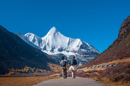 Male and female traveller at Yading Nature Reserve, Daocheng county, Ganzi Tibetan Autonomous Prefecture, Sichuan province of China. The holy peak Yangmaiyong (Jampelyang) can been seen in the background, In Autumn scenery.