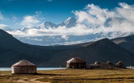 The yurt village in front of Karakul Lake in Xinjiang Uighur Autonomous Region of China is the highest lake of the Pamir plateau, with Muztagh Ata peak of the Kunlun mountains, in the background. Stok Fotoğraf - 111359310