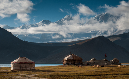 The yurt village in front of Karakul Lake in Xinjiang Uighur Autonomous Region of China is the highest lake of the Pamir plateau, with Muztagh Ata peak of the Kunlun mountains, in the background. Stok Fotoğraf - 111359311