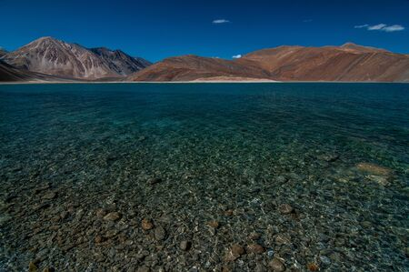 View of Lake Pangong with beautiful mountains in blue sky and reflection. Leh Ladakh, India