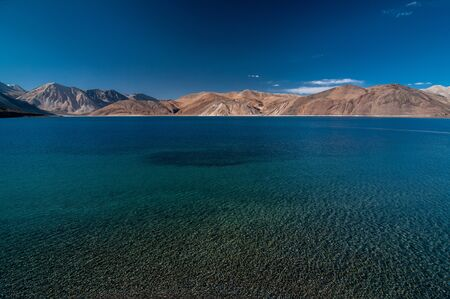 View of Lake Pangong with beautiful mountains in blue sky and reflection. Leh Ladakh, India Stok Fotoğraf - 133457084