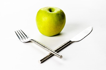 A green apple and a knife and a fork photo