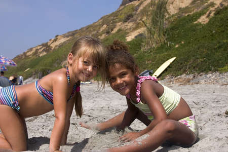 children at play: two cute girls playing in the sand at the beach. Stock Photo