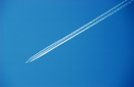 longing: a plane with contrails in the blue sky longing for your next vacation Stock Photo
