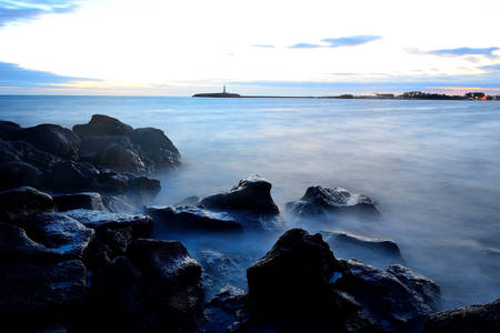 Sea at sunset with motion waves due to a long exposure, rocks on foreground