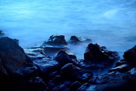 Sea at sunset with motion waves due to a long exposure, rocks on foreground Фото со стока - 38708351