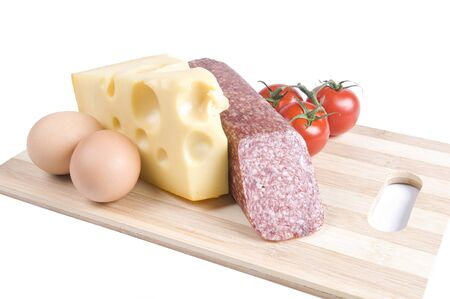Eggs, cheese, sausage and tomatoes on a board. Isolated over white photo