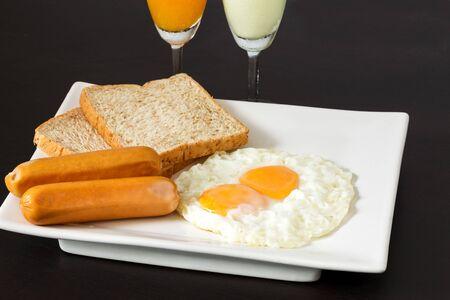 plato del buen comer: Huevos fritos con salchichas y pan en la placa blanca en juego de desayuno Foto de archivo