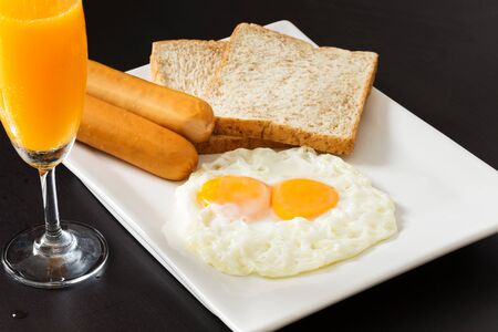 original plate: Fried eggs with sausages and bread on the white plate in breakfast set Stock Photo