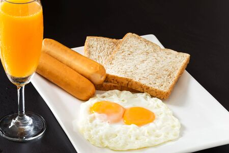 plato del buen comer: Fried eggs with sausages and bread on the white plate in breakfast set Foto de archivo