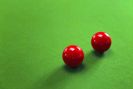 Two red snooker balls on green table selective focus