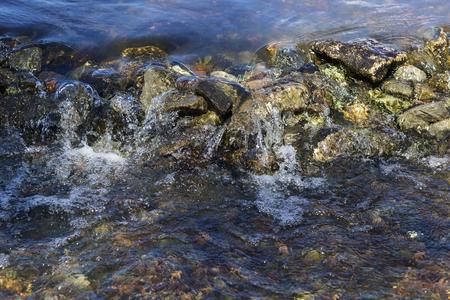 Stream flowing over stones rough rocks selective focus