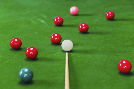 Selective focus on white snooker ball on green table and cue in foreground Banque d'images
