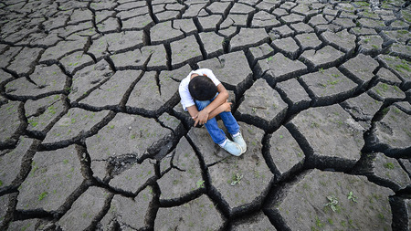 sitting on the ground: Sad boy sitting on Cracks ground Stock Photo