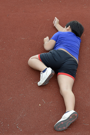 lay down: Young Asian boy tried and lay down on the running track