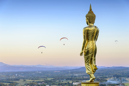 sagar: the standing Buddha statue in Nan province,Thailand with the para-motor player at the evening