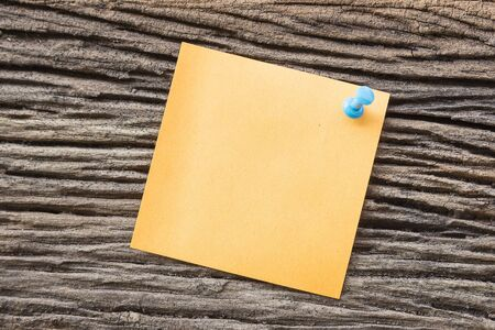 sticky paper: sticky paper note holding by pin on the old wooden background