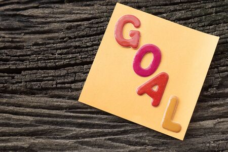 sticky paper: goal word on sticky paper note with the old wooden background