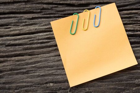 sticky paper: sticky paper note holding by clip on the old wooden background Stock Photo