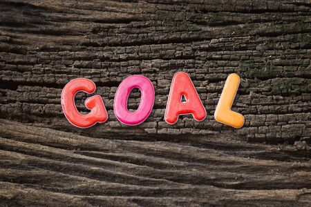 sticky paper: goal word on sticky paper note and paper clip with the old wooden background Stock Photo