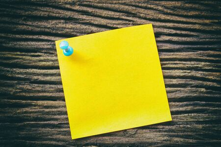 sticky paper: yellow sticky paper note holding by pin on the old wooden background with vintage scene