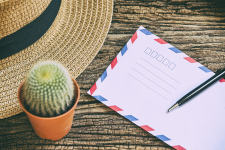 envelop: the envelop and the pen on the wooden background table with the hat and cactus Stock Photo