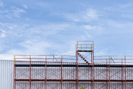 The red scaffold at the factory building between renovate process Stock Photo