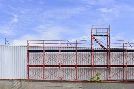 scaffolder: The red scaffold at the factory building between renovate process Stock Photo