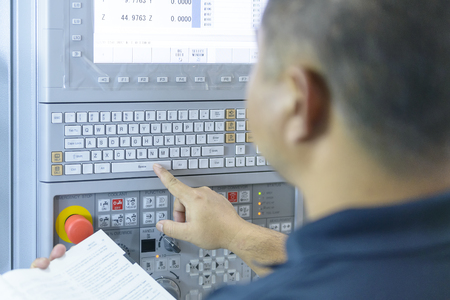 experienced operator: The CNC panel with the operator.The CNC machine operation by CNC operator with the manual book.