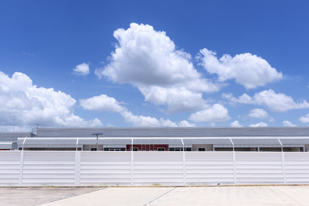 parking facilities: The factory building with concrete fence foreground and the blue sky
