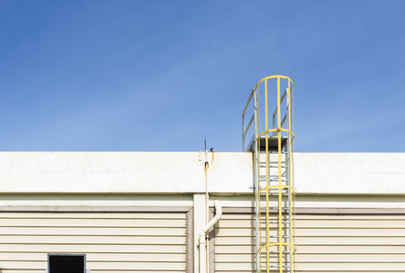emergency stair: The yellow fire escape stair attach at the factory building with the blue sky Stock Photo