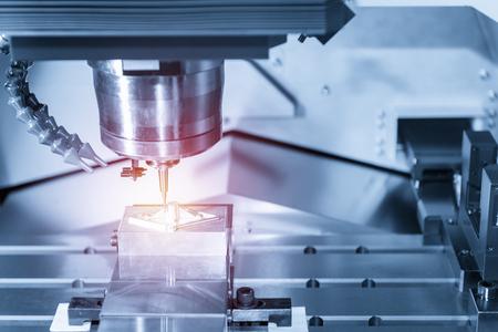 De CNC-freesmachine, terwijl het monsterwerkstuk in blauw-zilveren toon en verlichtingseffect wordt gesneden Stockfoto