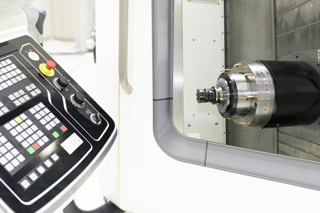 Close up of the horizontal spindle of CNC Machine and the cutting tool with the control panel Banco de Imagens