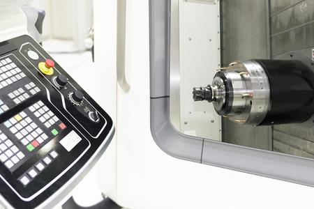 Zbliżenie poziomego wrzeciona maszyny CNC i narzędzia tnącego z panelem sterowania Zdjęcie Seryjne